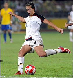 Carli Lloyd plants her foot before using the other to kick a soccer ball.
