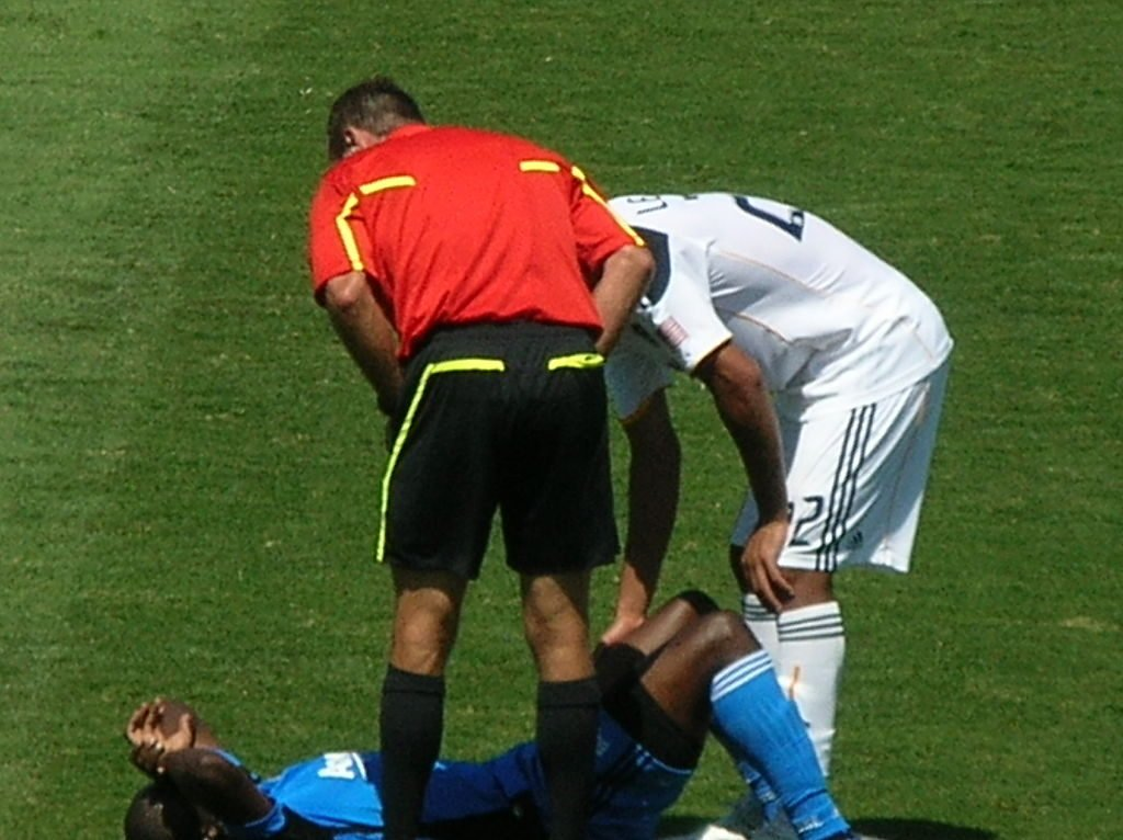 Soccer player lying injured on the field.