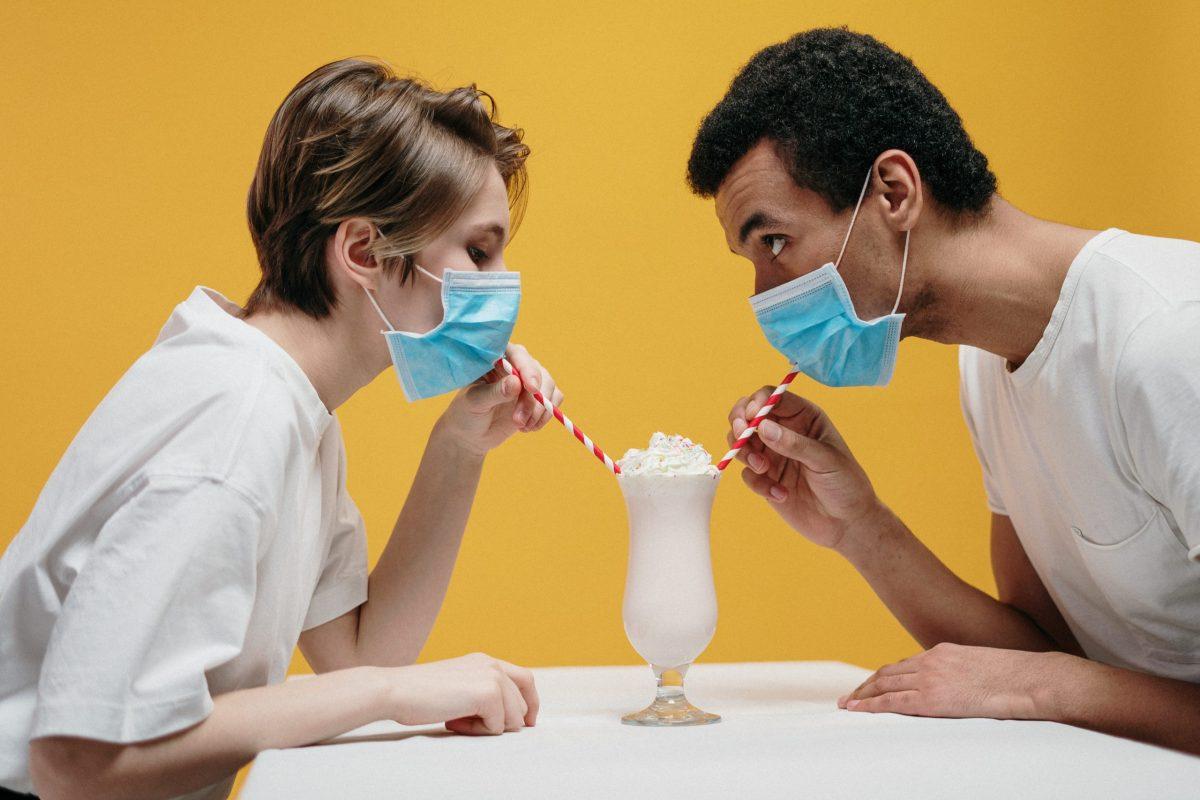 Two people sharing a milkshake while wearing masks